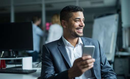 man smiling while using cell phone