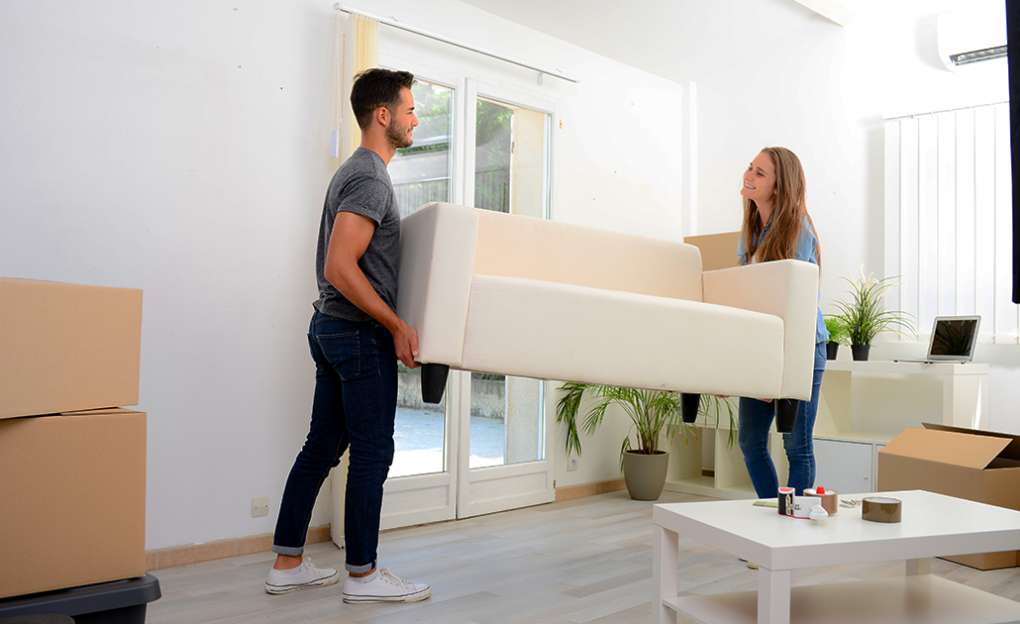 A young couple moving a large couch.
