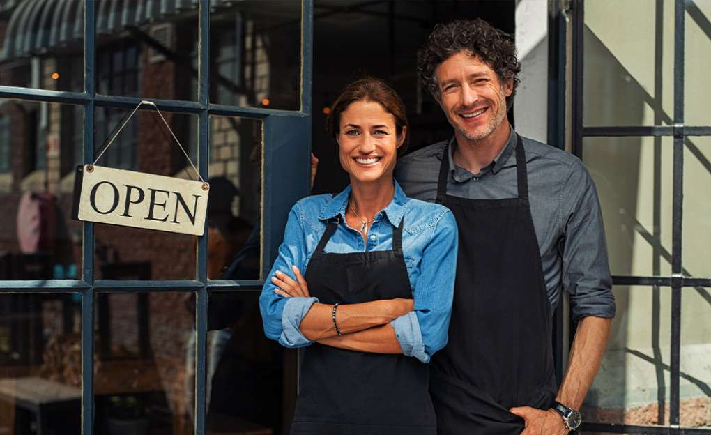 A couple stands proudly in front of the OPEN sign hanging on the front of their small business.