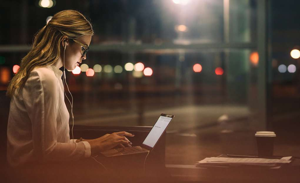 A young woman working on her laptop late at night