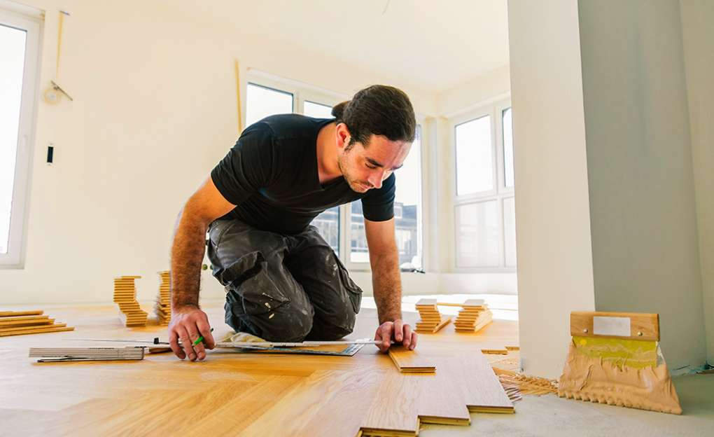A young man installing hard wood floor in a home.