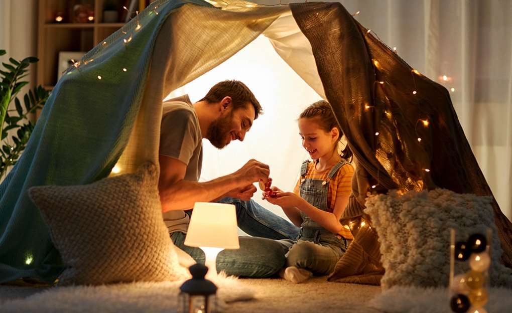 dad and daughter inside a fort made of blankets playing