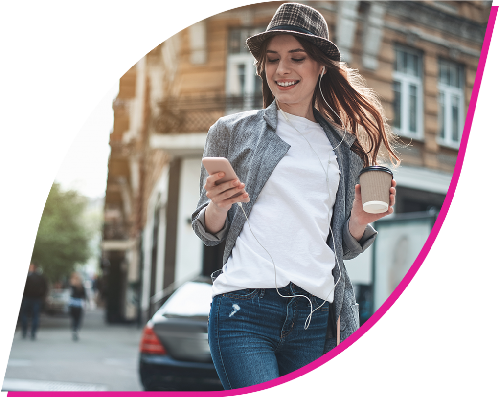 Young woman wearing a hat and walking down a city street while looking at her phone and holding a coffee.