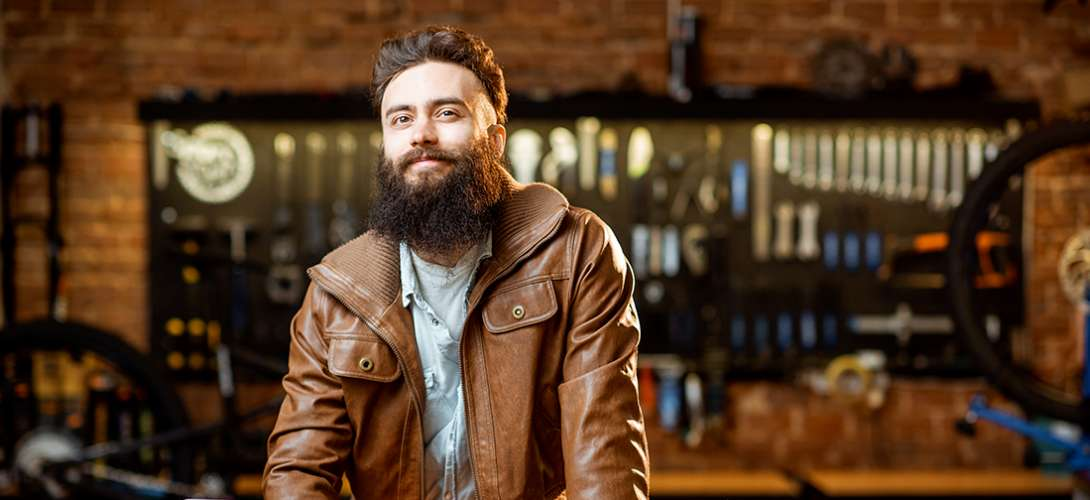 A man with a beard and a brown leather jacket stands in front of a bar.