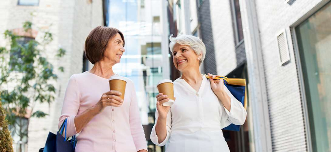Two older women share coffee.